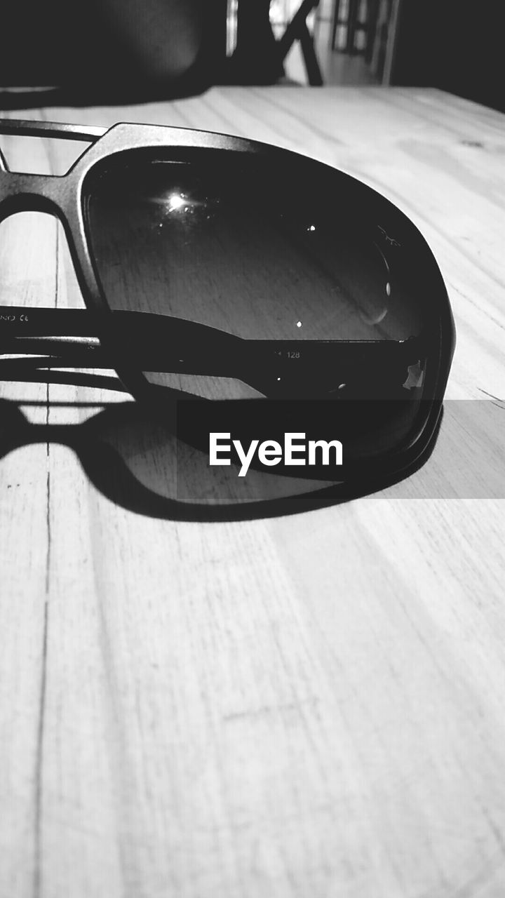 CLOSE UP OF SUNGLASSES ON TABLE