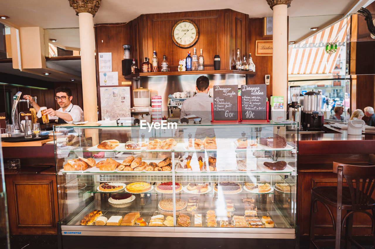 food and drink, real people, food, men, indoors, business, adult, group of people, standing, women, choice, store, retail, mid adult, males, restaurant, people, young men, transparent, sweet food, display cabinet, retail display