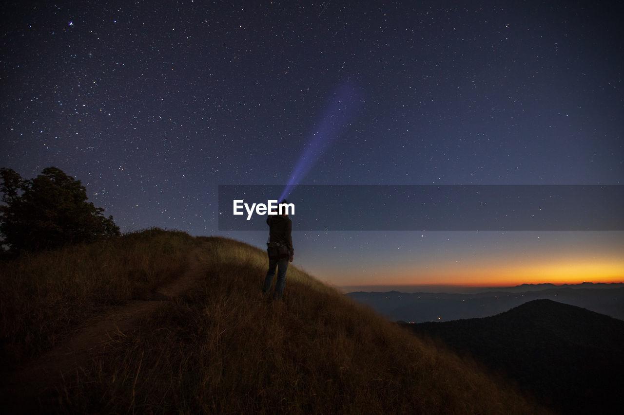 Tourist with illuminated flashlight standing on mountain against star field at night
