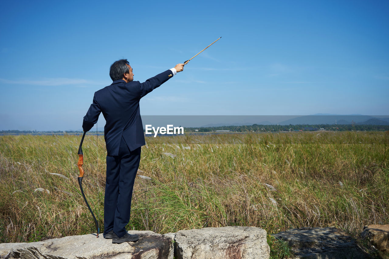 Businessman With Bow And Arrow On Field Against Sky