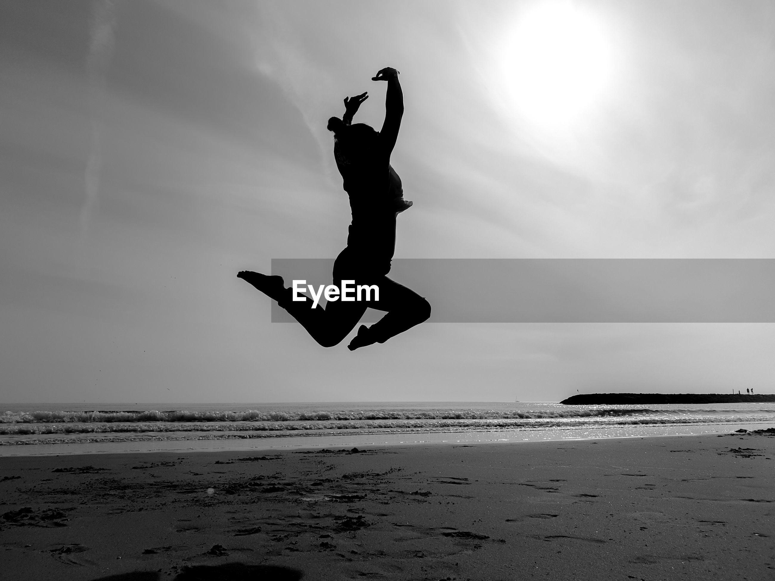 SILHOUETTE MAN JUMPING ON BEACH