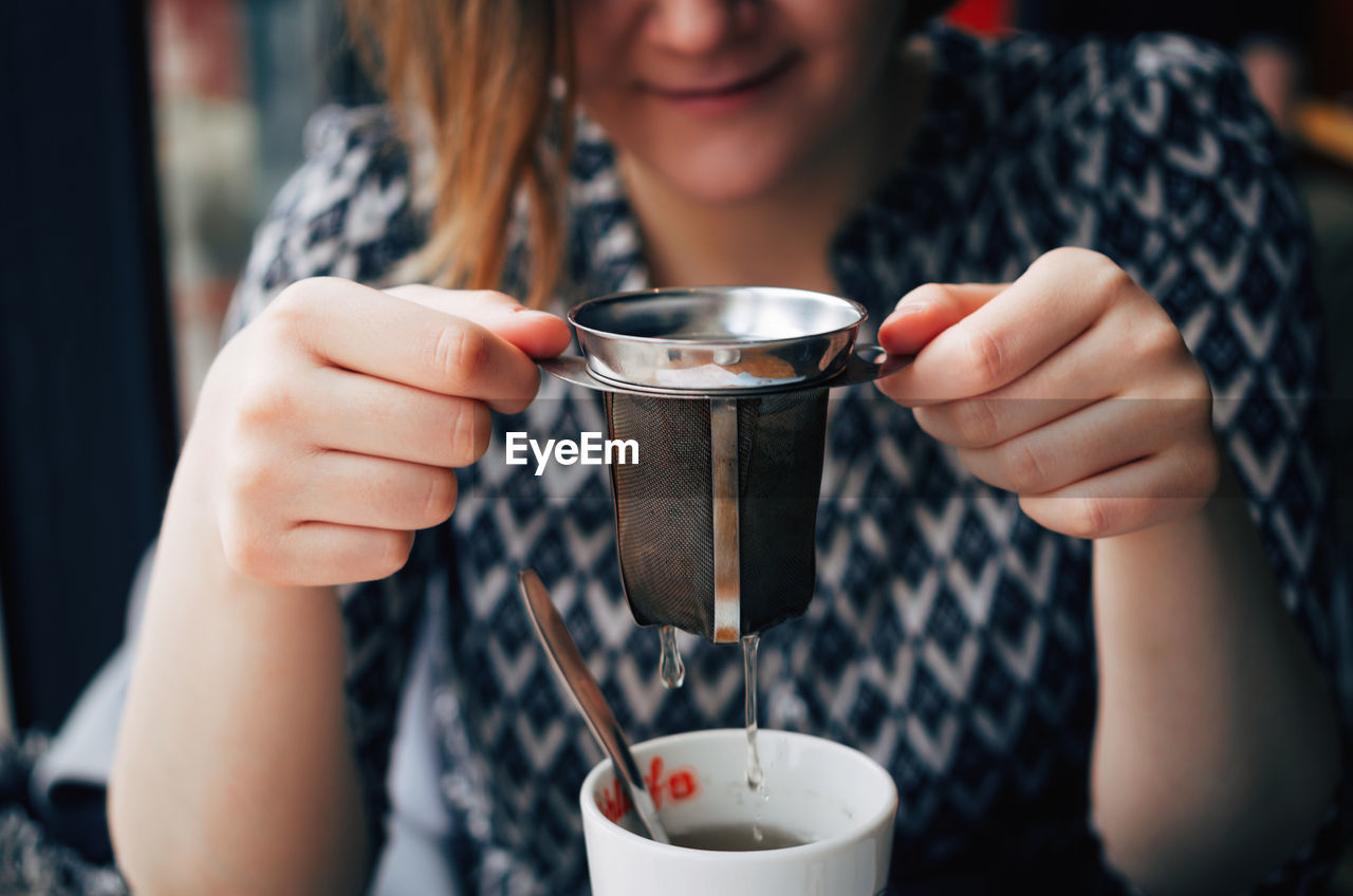 Midsection Of Young Woman Holding Infuser Over Tea Cup At Restaurant