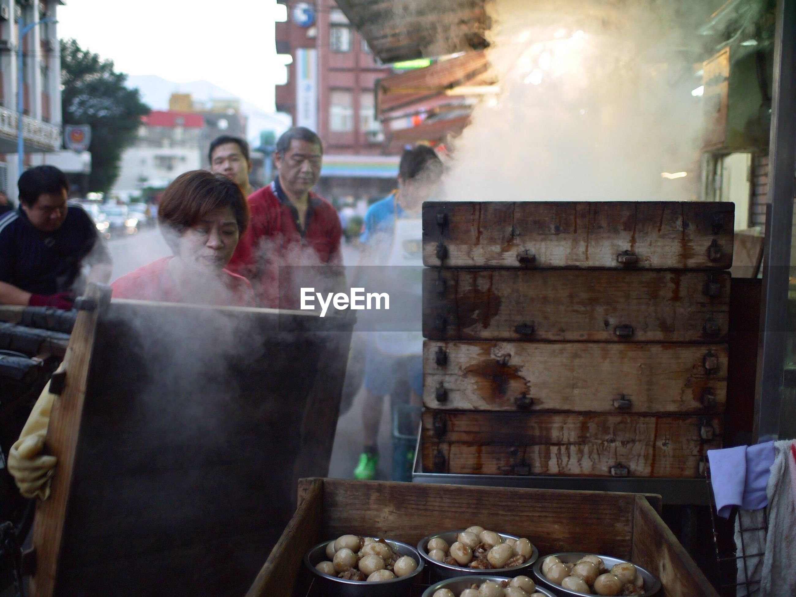 men, lifestyles, food and drink, person, leisure activity, standing, market stall, medium group of people, market, rear view, incidental people, large group of people, smoke - physical structure, outdoors, building exterior, casual clothing, food, built structure