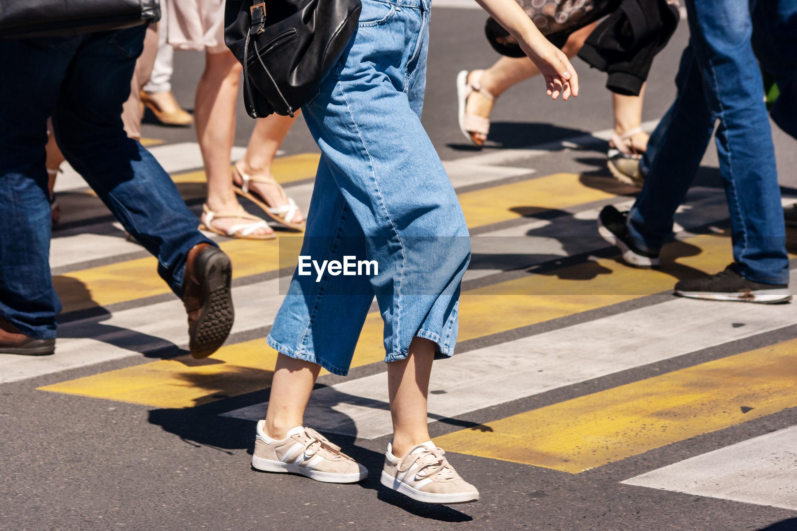 Low section of people walking on crosswalk