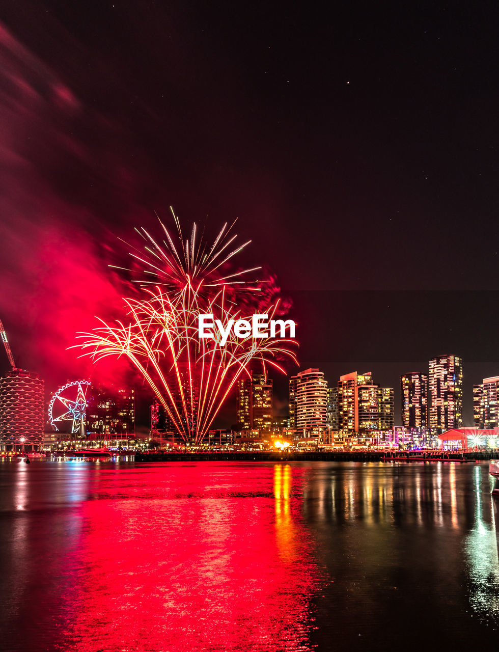 illuminated, night, water, architecture, building exterior, reflection, built structure, waterfront, firework, sky, motion, river, city, firework display, celebration, exploding, arts culture and entertainment, no people, long exposure, cityscape, outdoors, light, office building exterior, firework - man made object, skyscraper, nightlife