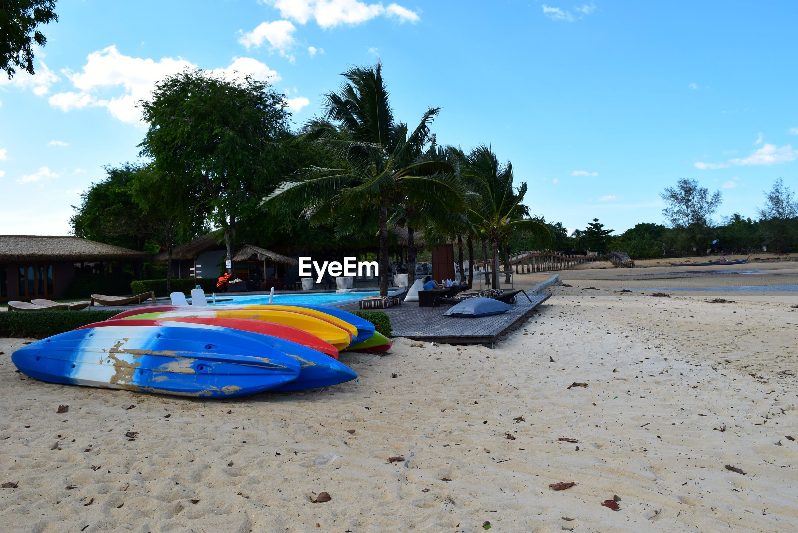 tree, beach, sand, sky, blue, transportation, palm tree, moored, shore, water, mode of transport, nautical vessel, tranquility, sunlight, incidental people, boat, day, nature, cloud, cloud - sky
