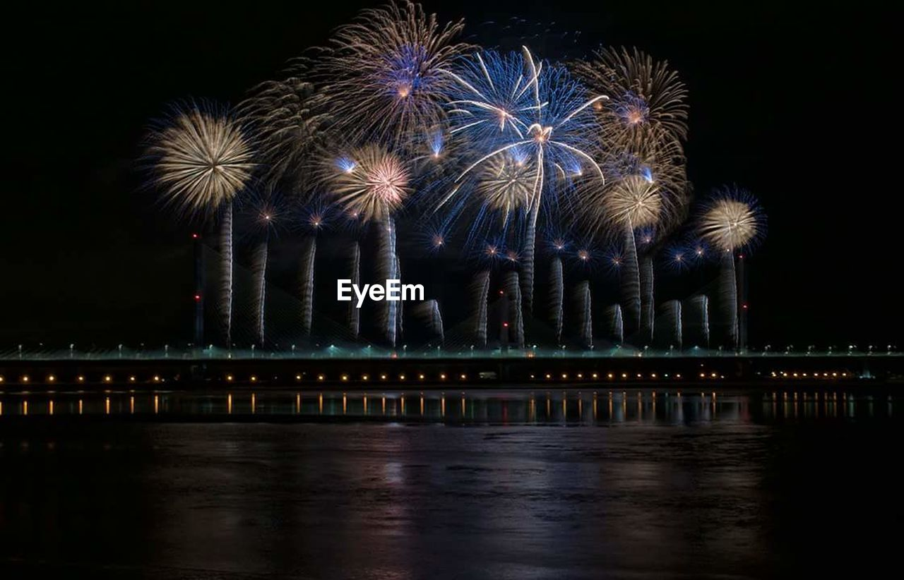 night, firework, illuminated, motion, firework display, arts culture and entertainment, sky, architecture, water, exploding, reflection, celebration, long exposure, event, built structure, firework - man made object, blurred motion, no people, nature, outdoors, light, sparks
