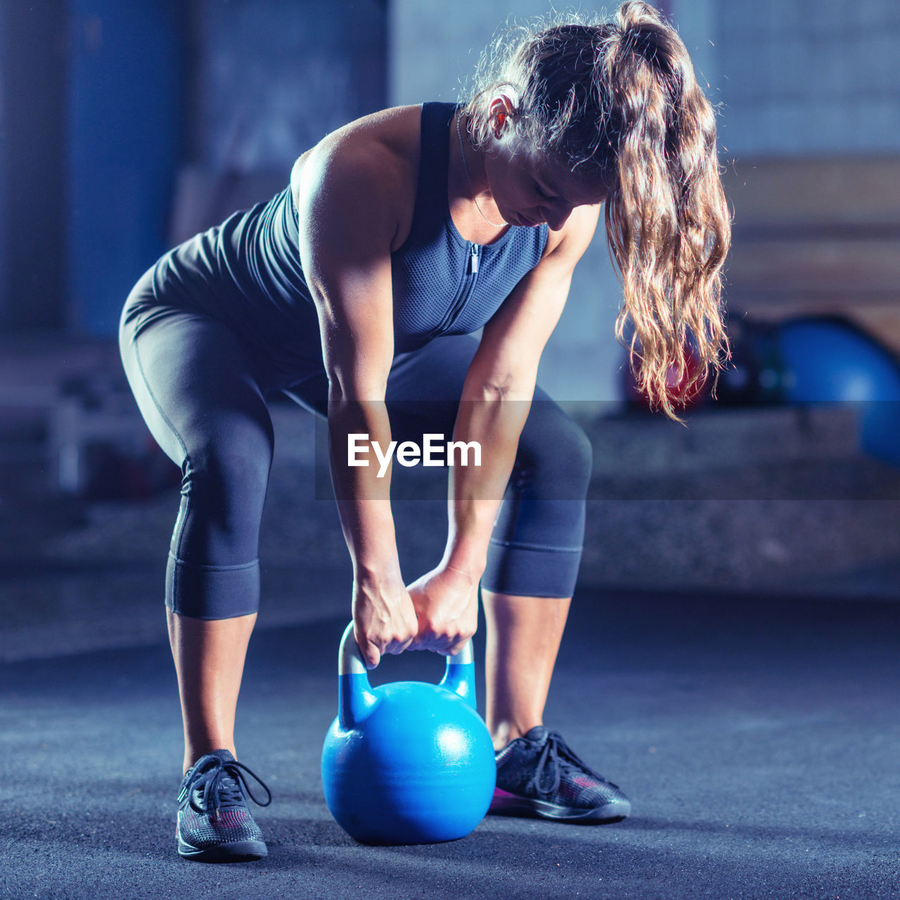 lifestyles, exercising, strength, sport, healthy lifestyle, real people, sports clothing, full length, one person, indoors, young women, sports training, young adult, clothing, muscular build, women, vitality, athlete, focus on foreground, weight training, physical activity, body conscious, effort, beautiful woman