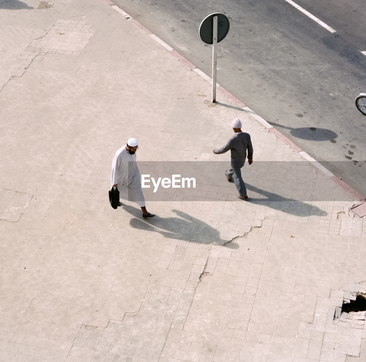 HIGH ANGLE VIEW OF TWO MEN STANDING ON STREET