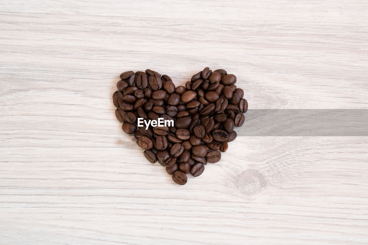 High Angle View Of Heart Shape Made Of Roasted Coffee Beans On Table