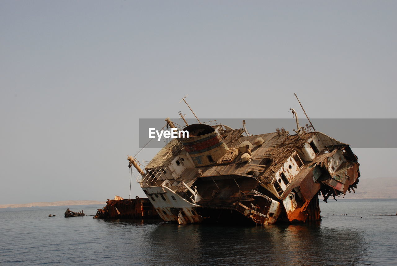 sky, nautical vessel, sea, transportation, clear sky, water, mode of transportation, nature, ship, shipwreck, copy space, abandoned, damaged, decline, deterioration, no people, run-down, accidents and disasters, obsolete, outdoors, ruined, sinking, demolished