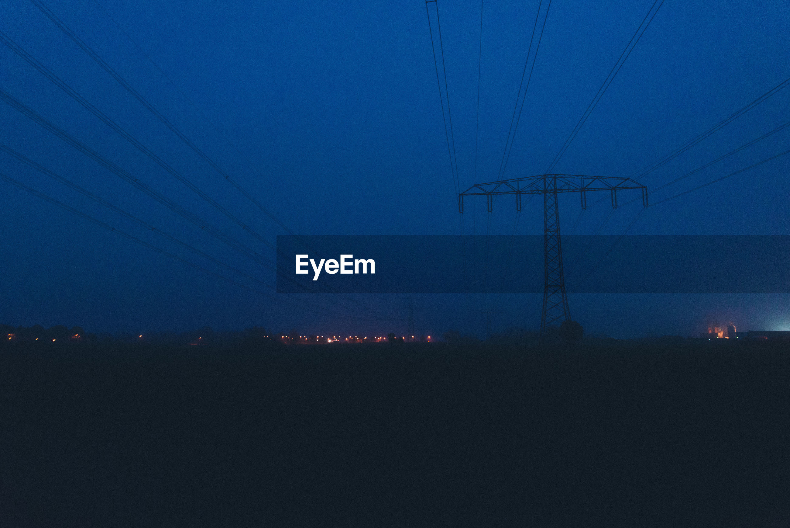 SILHOUETTE ELECTRICITY PYLONS AGAINST SKY AT NIGHT
