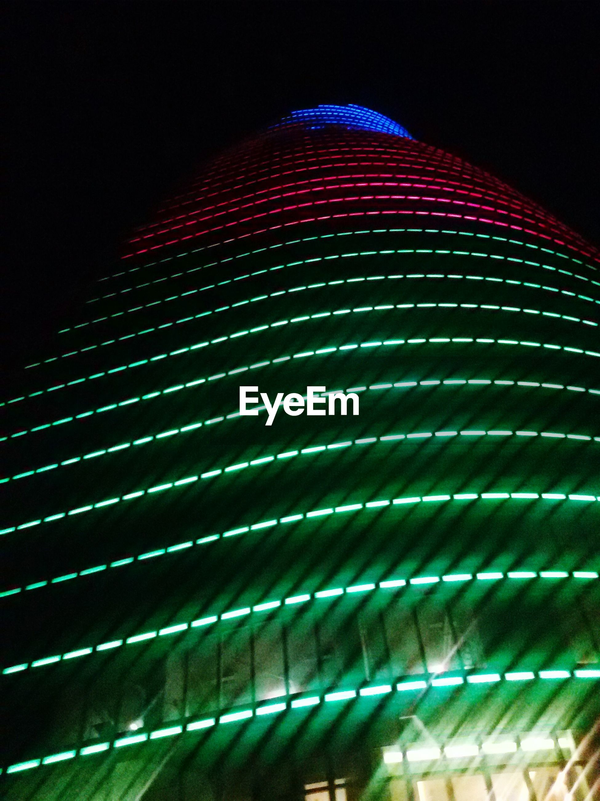illuminated, night, low angle view, pattern, modern, built structure, architecture, lighting equipment, building exterior, no people, design, indoors, light - natural phenomenon, glowing, repetition, close-up, railing, city, skyscraper