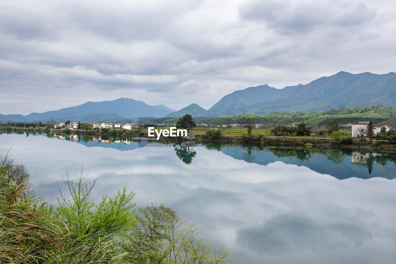 cloud - sky, mountain, water, sky, scenics - nature, tranquil scene, beauty in nature, tranquility, lake, mountain range, reflection, nature, day, plant, tree, non-urban scene, no people, waterfront, idyllic, outdoors