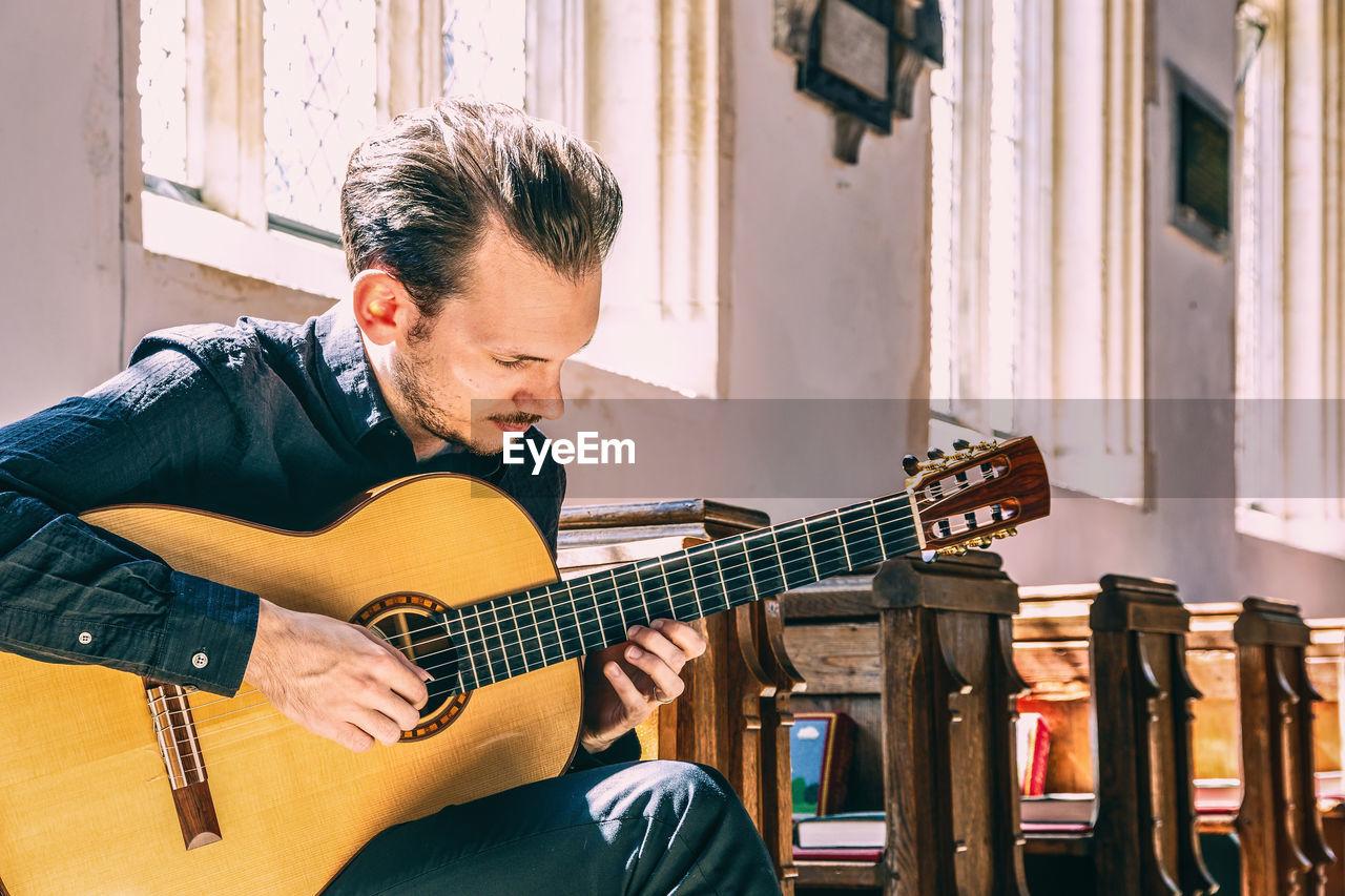 Man playing guitar while sitting at table