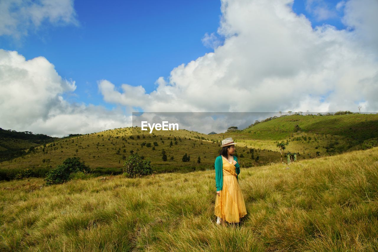 Mid adult woman standing on green landscape against sky