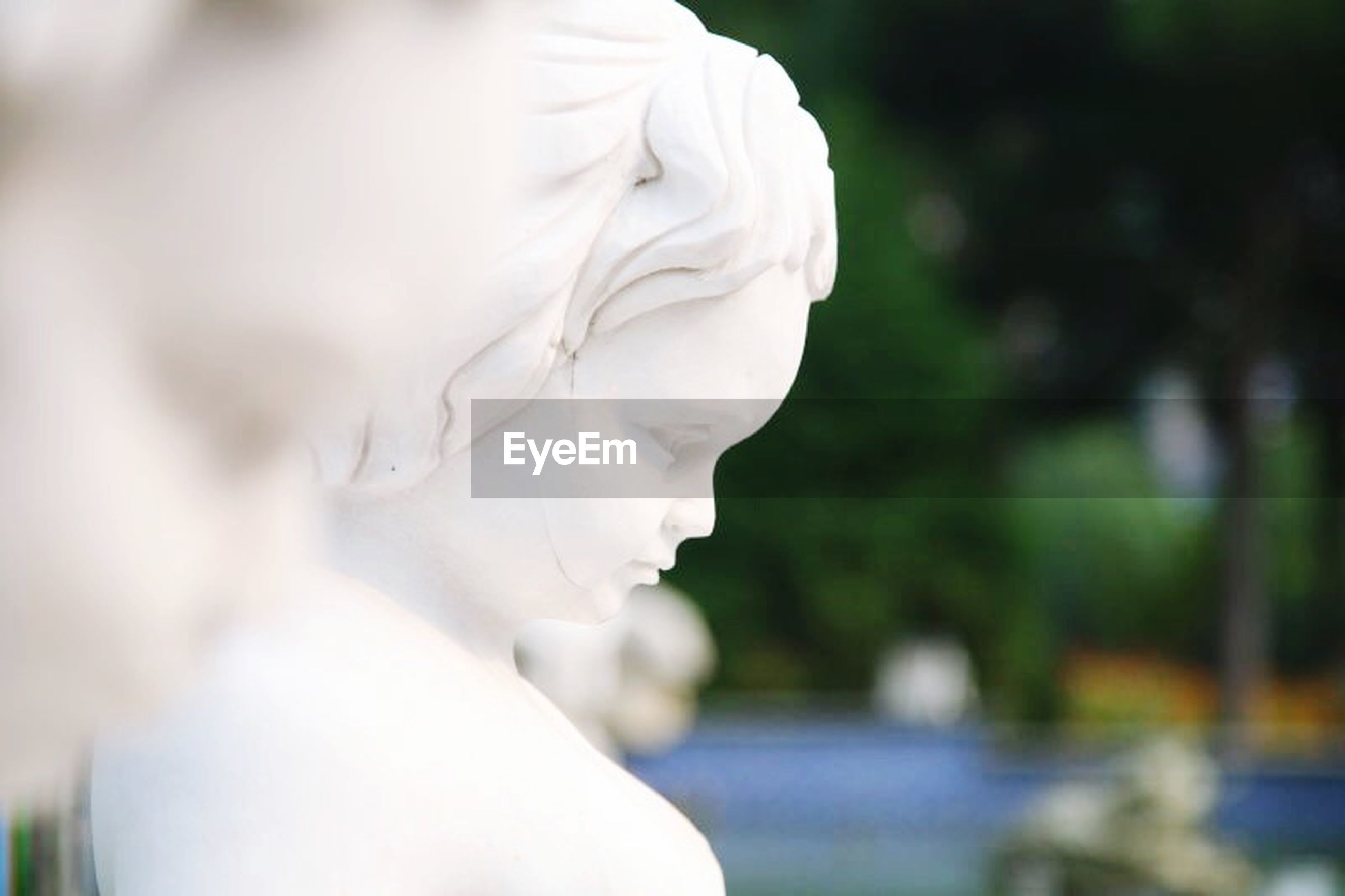 focus on foreground, close-up, selective focus, person, holding, flower, lifestyles, white color, human representation, part of, day, fragility, outdoors, sculpture, creativity