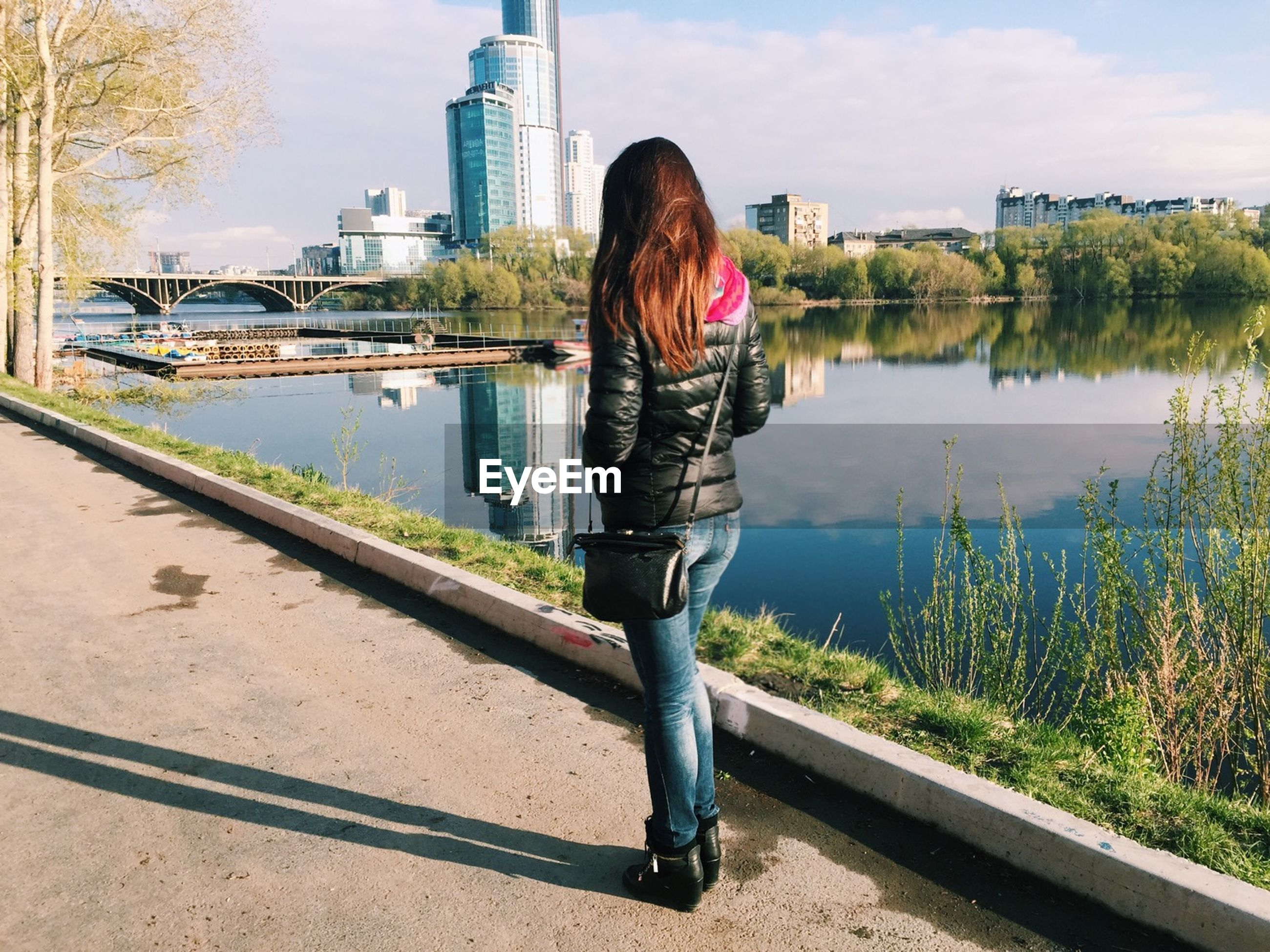 Rear view of woman with purse standing on sidewalk by pond against city