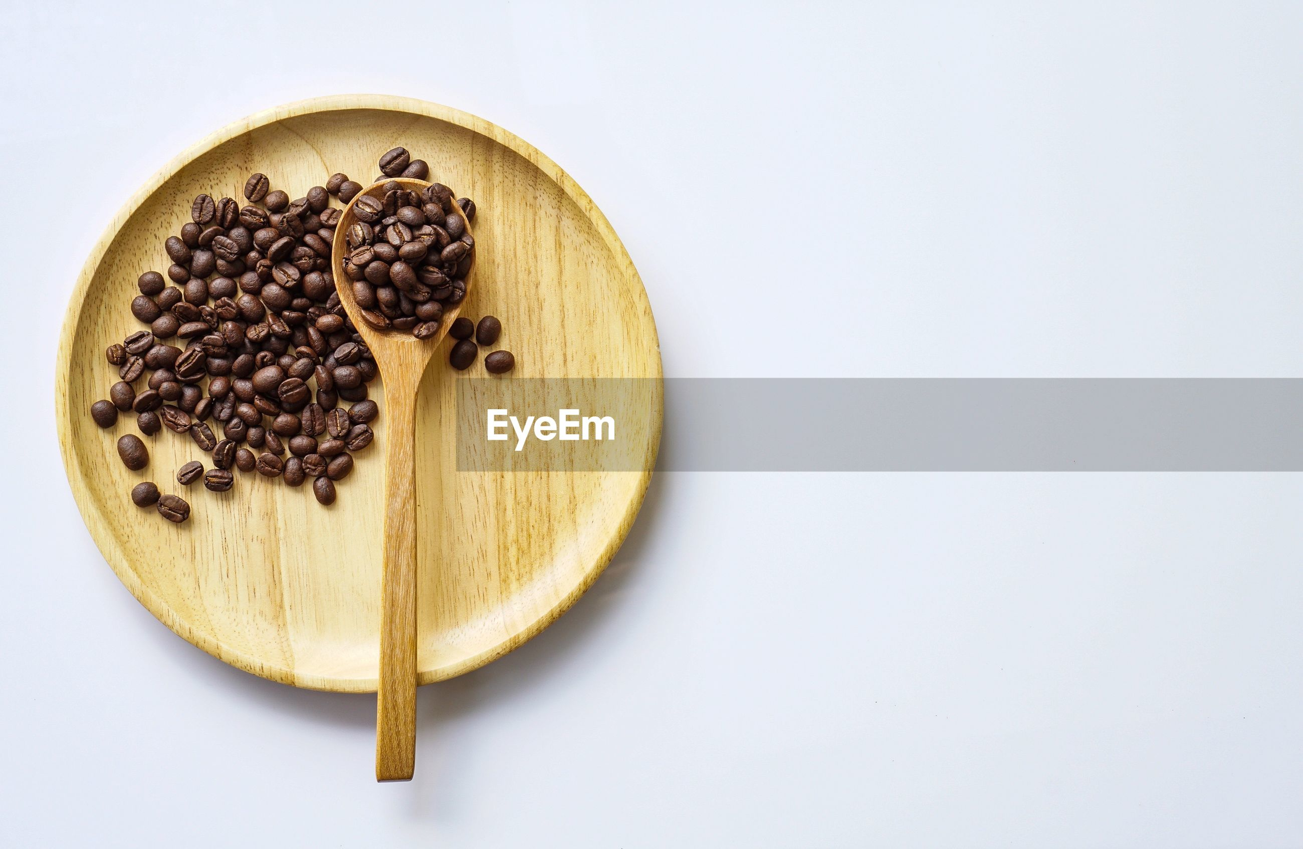 Directly above shot of roasted coffee beans in plate over white background