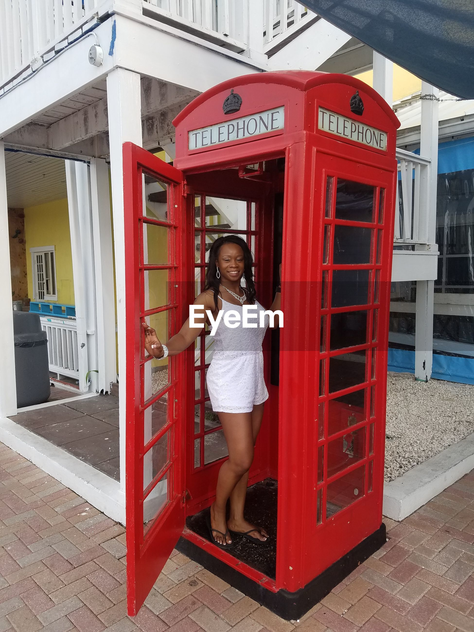 Portrait of smiling woman standing in telephone booth