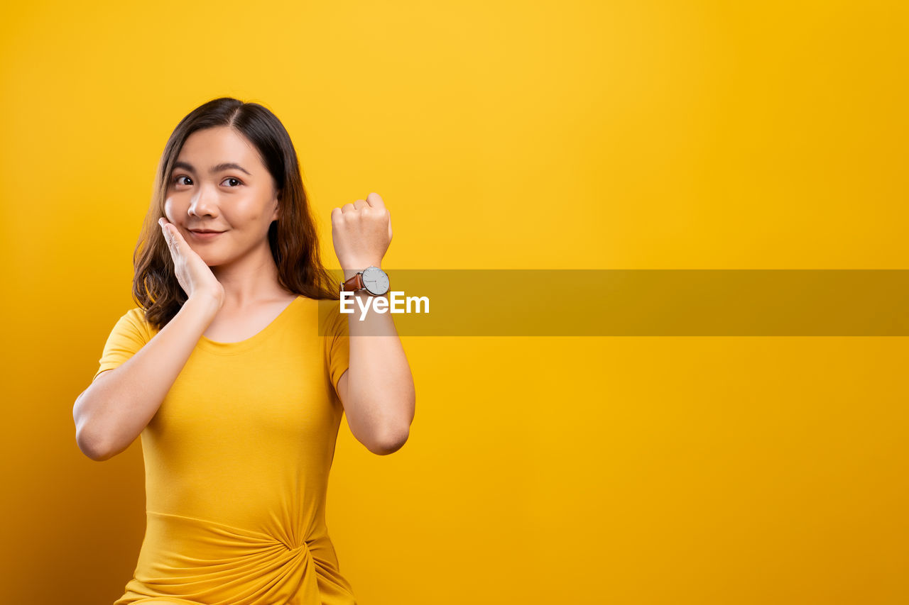 Young woman showing wristwatch while standing against yellow background