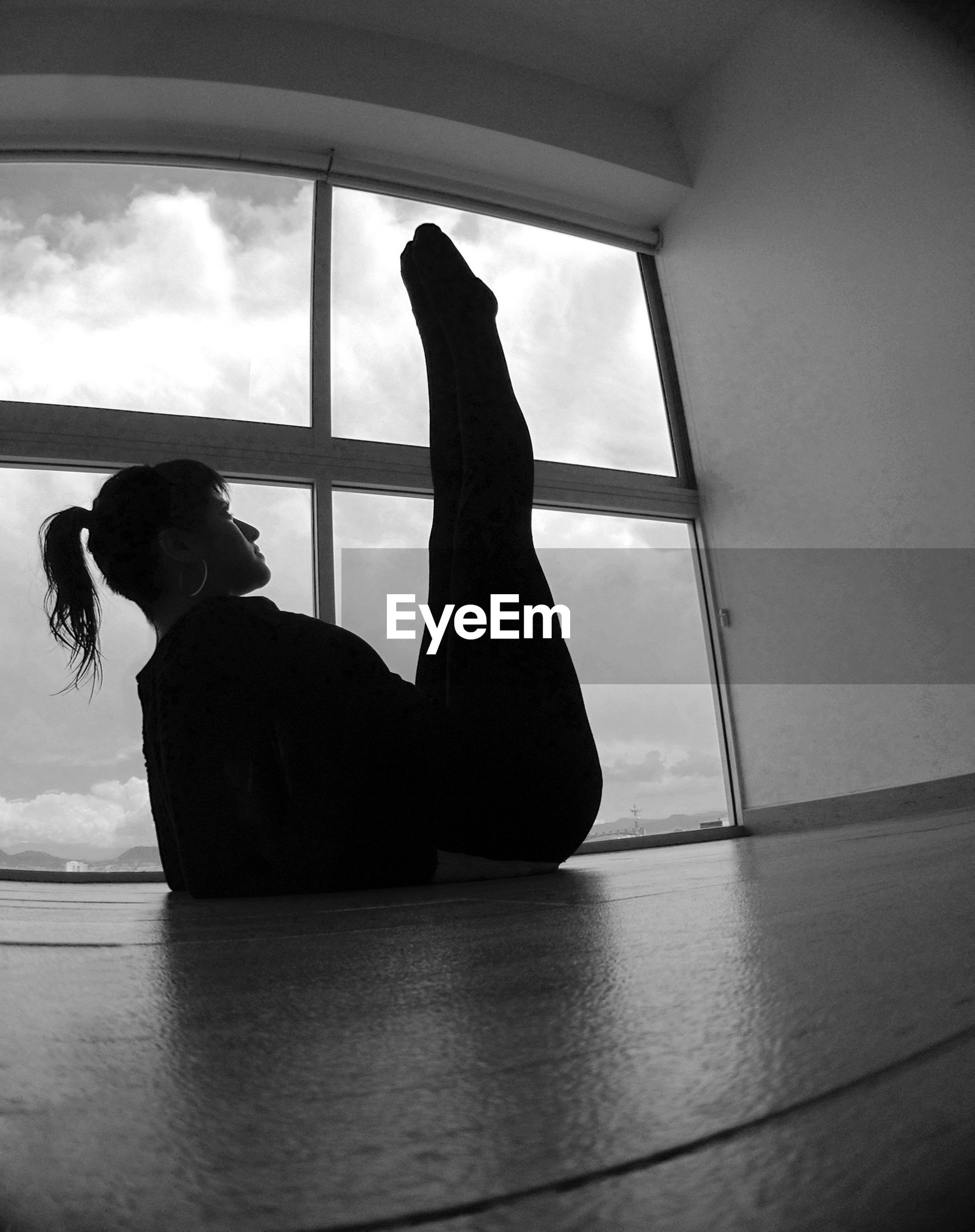 Low angle view of woman exercising against window