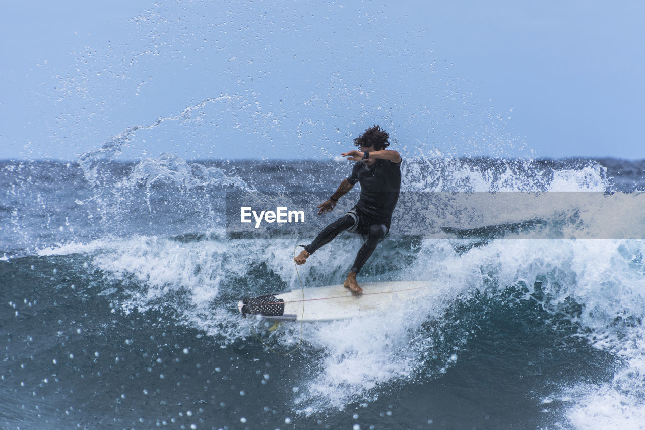 motion, sport, water, one person, sea, splashing, wave, extreme sports, aquatic sport, surfing, nature, leisure activity, adventure, day, full length, sky, young adult, clear sky, skill, outdoors, power in nature