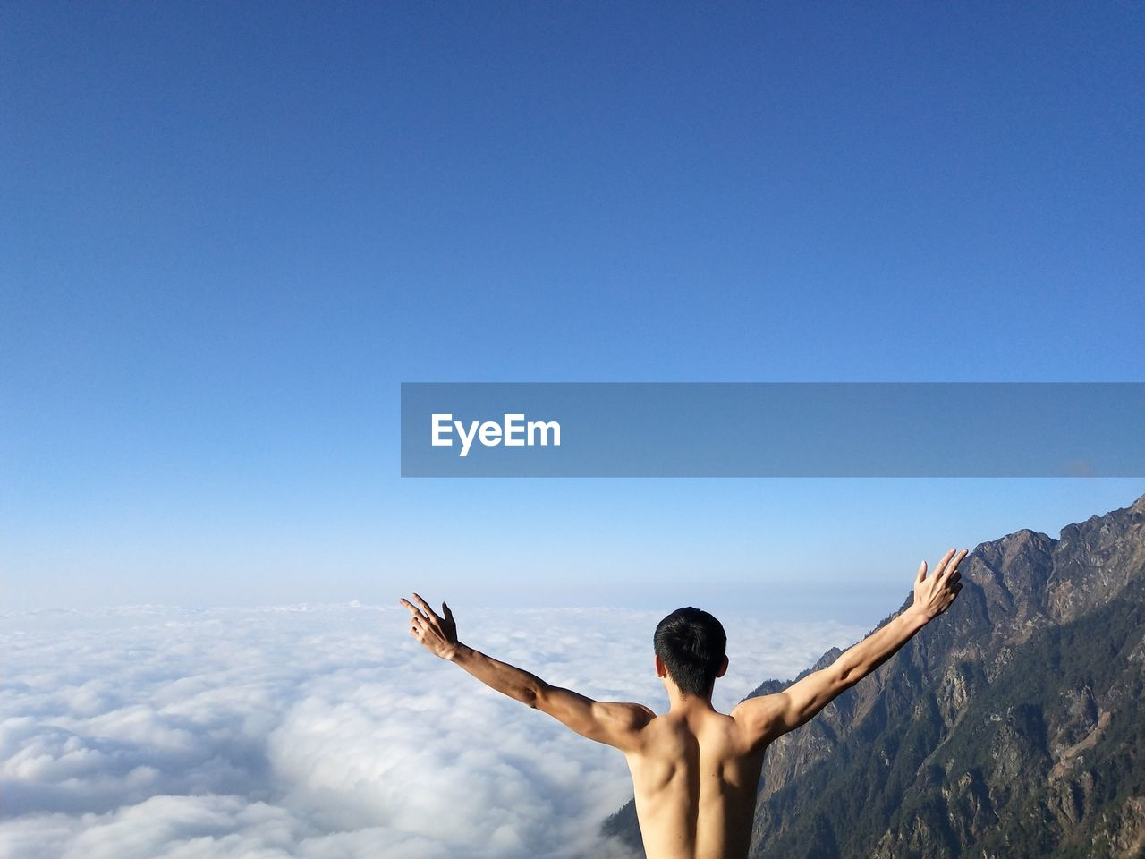 Rear view of shirtless man with arms outstretched standing against blue sky