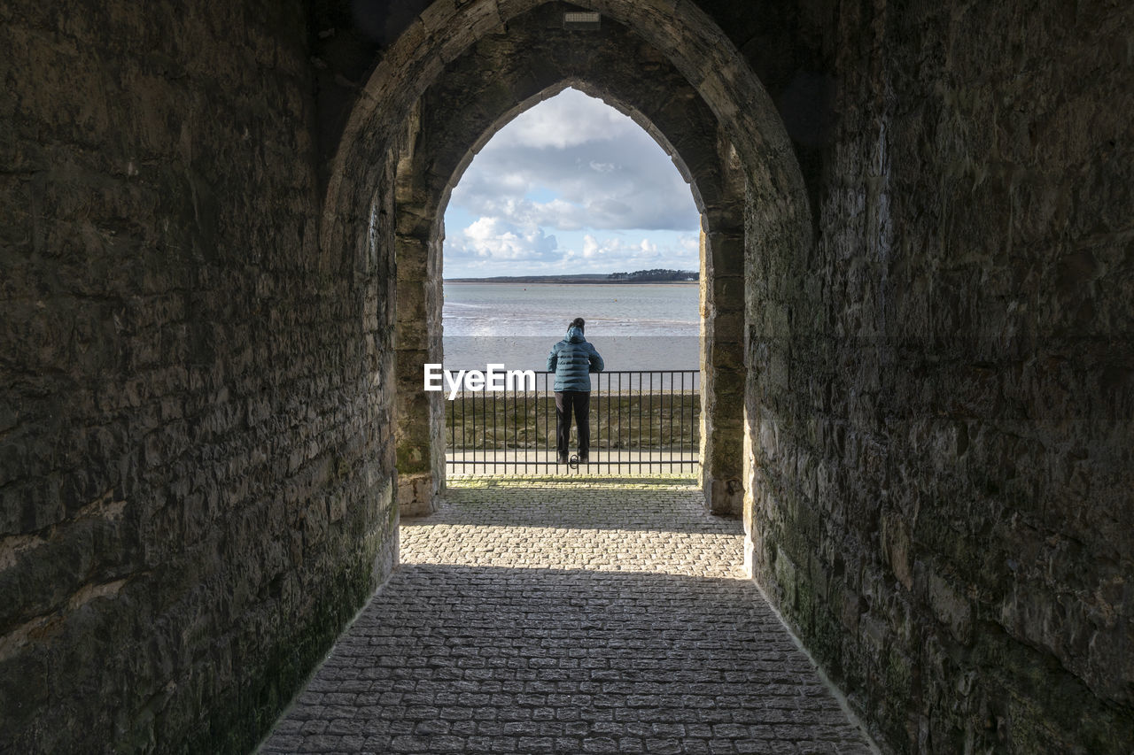 arch, architecture, built structure, cloud - sky, full length, one person, direction, sky, day, rear view, the way forward, real people, history, nature, wall, lifestyles, the past, women, adult, outdoors, stone wall