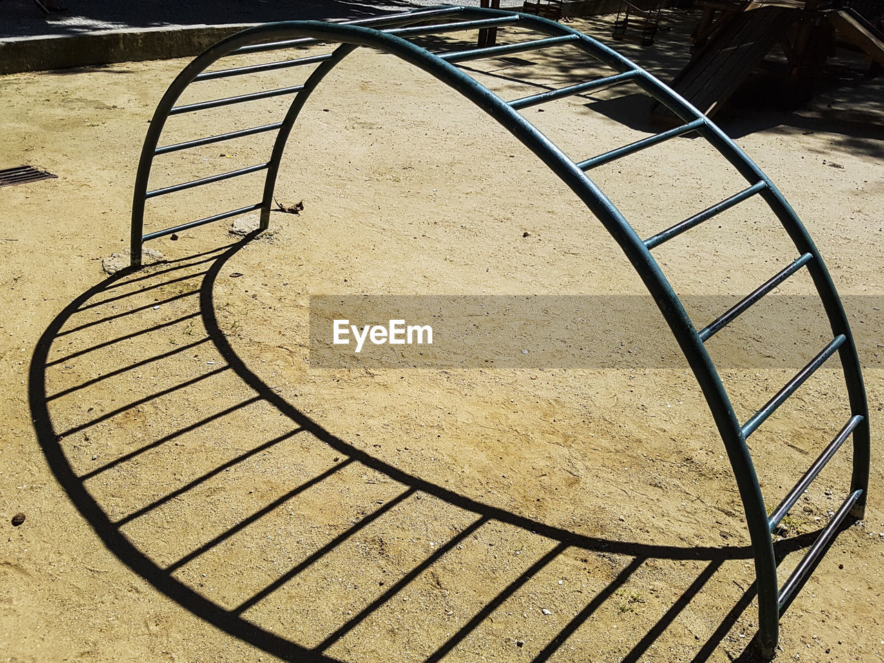 metal, high angle view, day, no people, sunlight, shadow, pattern, absence, railing, nature, empty, playground, outdoors, architecture, staircase, bicycle rack, built structure, spiral, footpath, in a row, focus on shadow