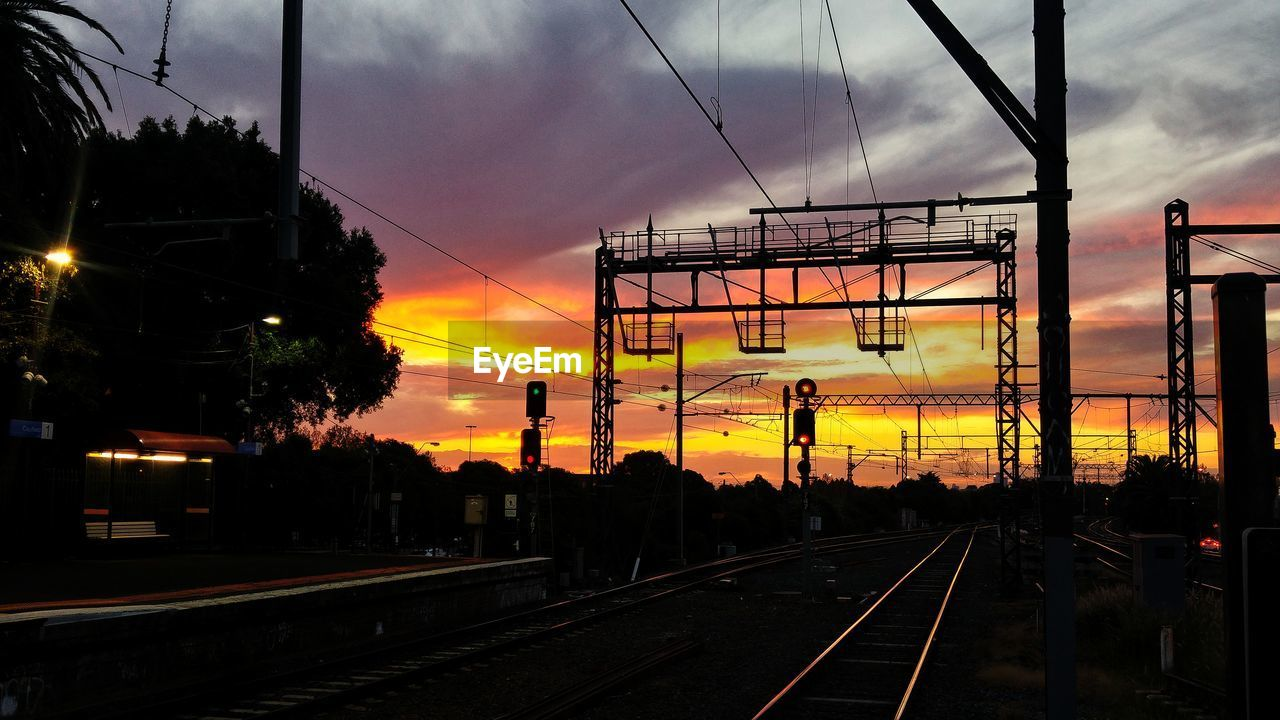 sunset, transportation, railroad track, rail transportation, sky, cloud - sky, cable, power line, electricity pylon, public transportation, dramatic sky, mode of transport, train - vehicle, silhouette, connection, no people, dusk, railway track, electricity, built structure, the way forward, nature, railway signal, outdoors, illuminated, technology, architecture, tree, city, day