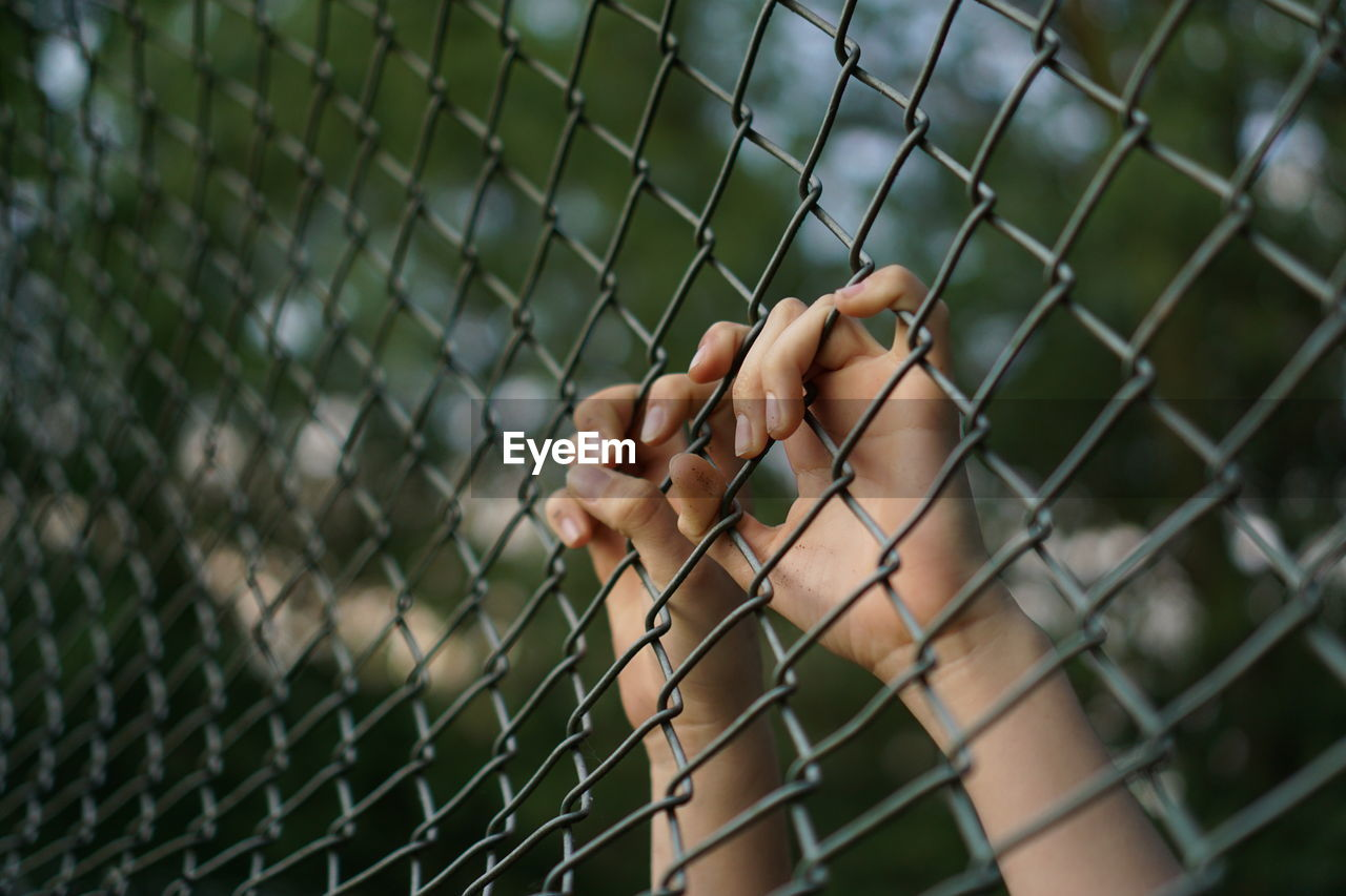 Cropped Hands Holding Chainlink Fence