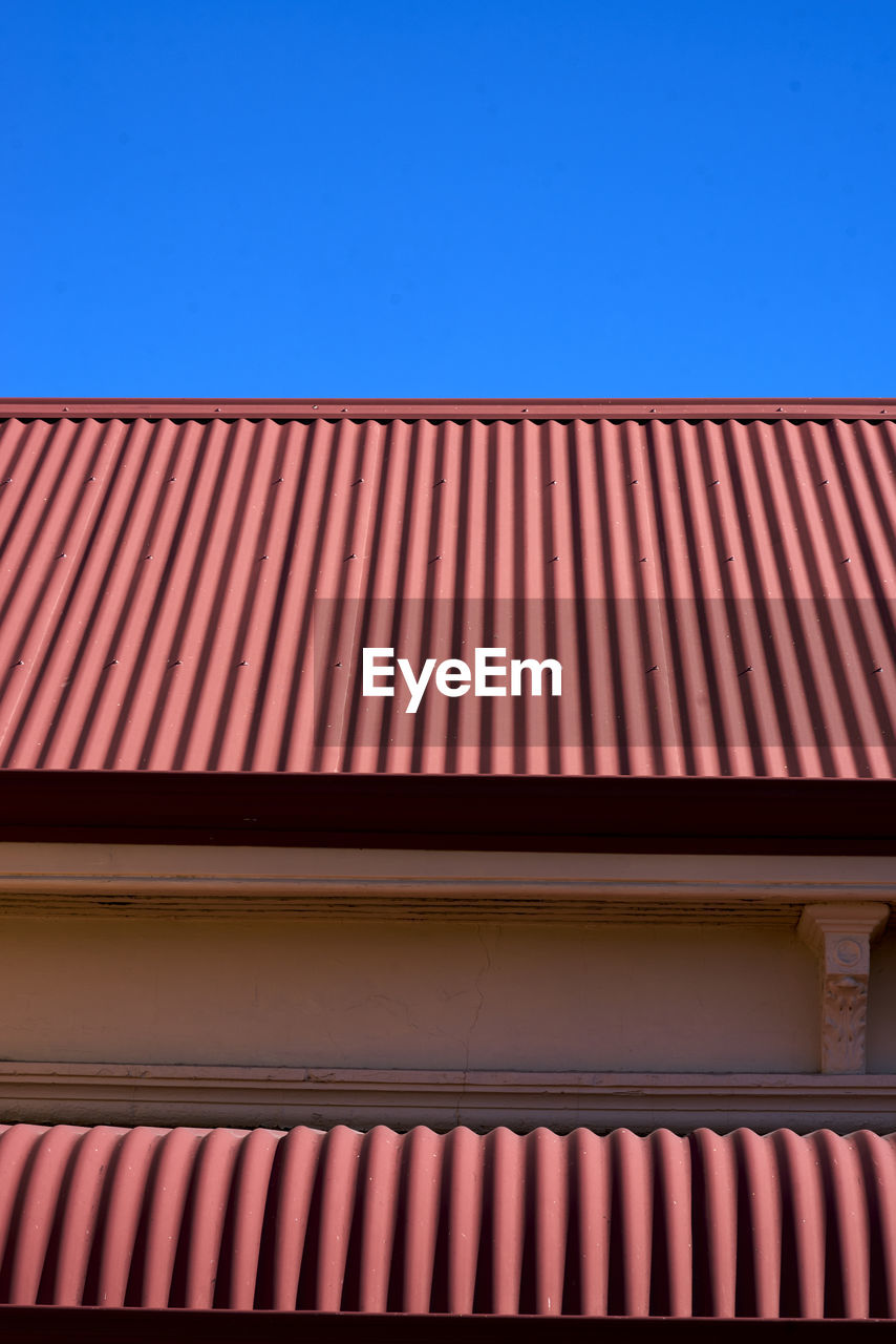 architecture, built structure, building exterior, blue, clear sky, sky, low angle view, pattern, no people, building, day, roof, corrugated iron, nature, copy space, iron, outdoors, wall - building feature, sunlight, metal, corrugated, roof tile