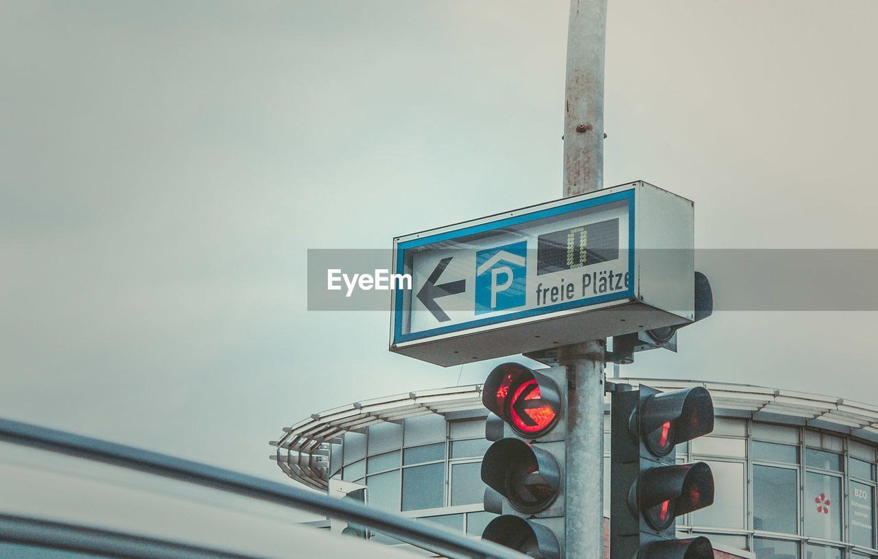 Low Angle View Of Road Sign And Signal On Pole Against Sky