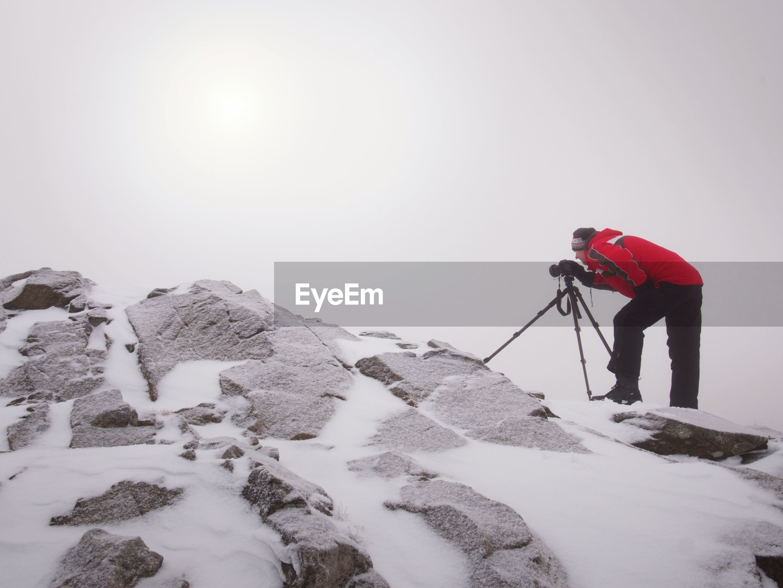 Man in warm clothes enjoy photographying in wild winter nature. snowy summit rock. listen to muse.