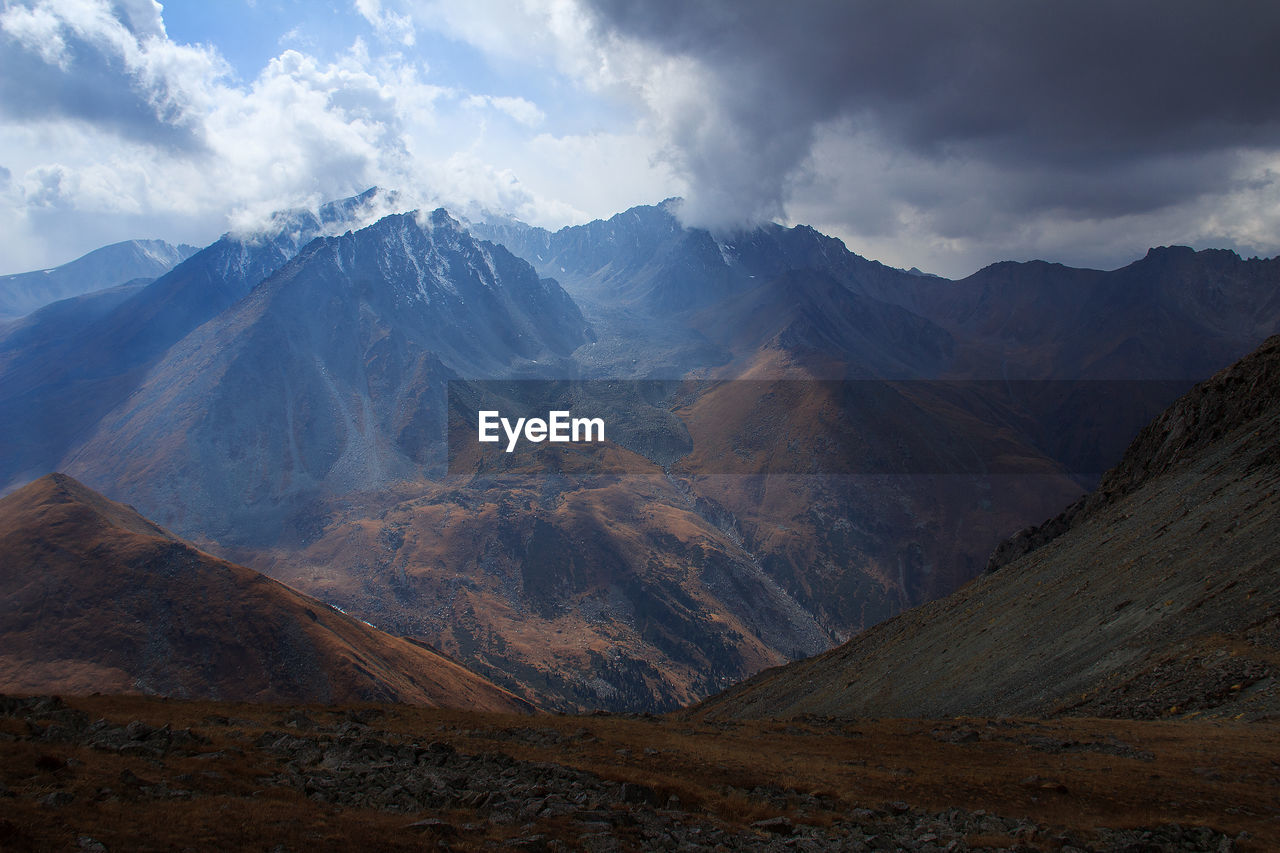 Alpine gorge with snow-capped peaks in sunlight in autumn, sky with clouds