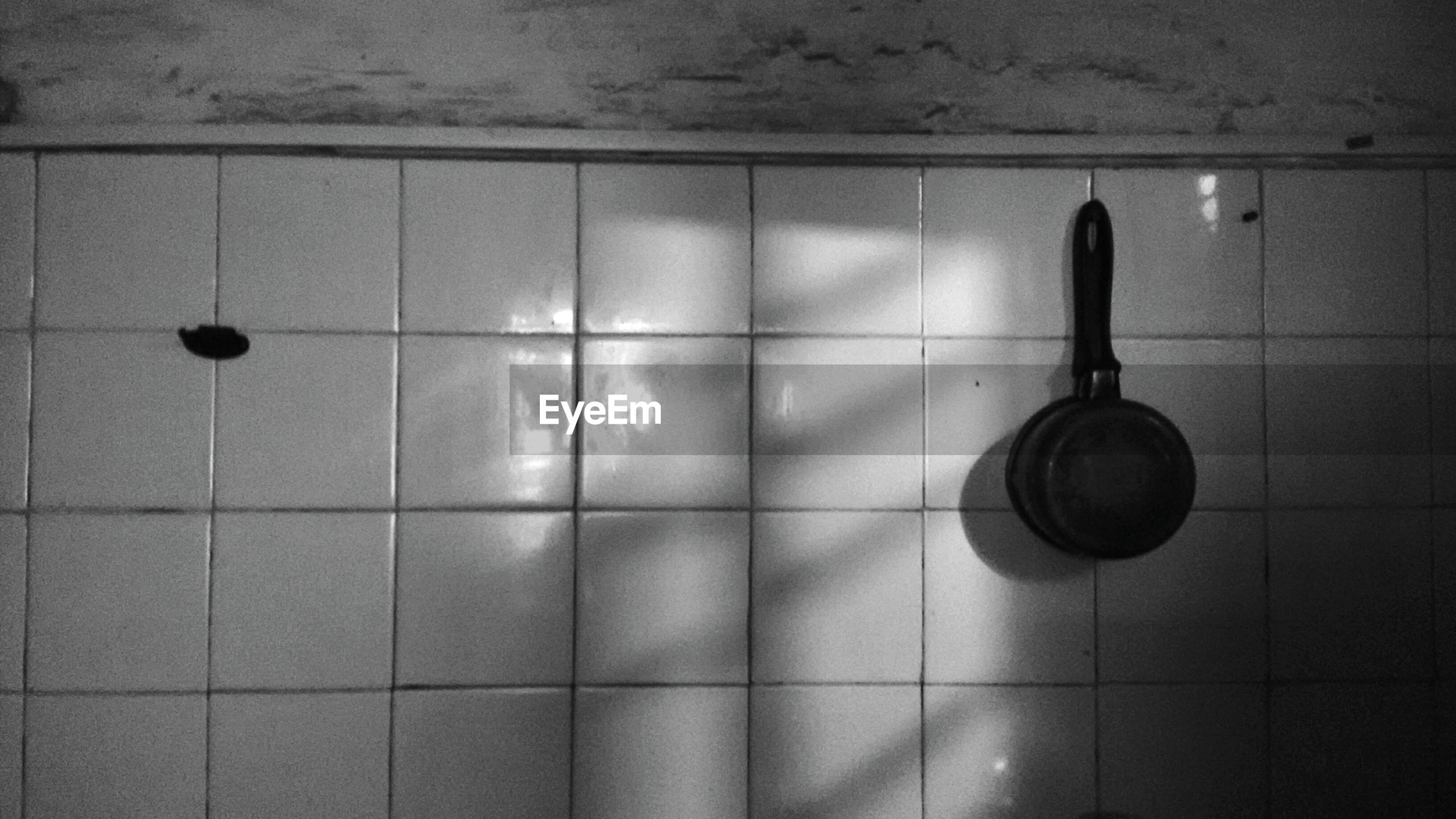Cooking pan hanging from kitchen wall