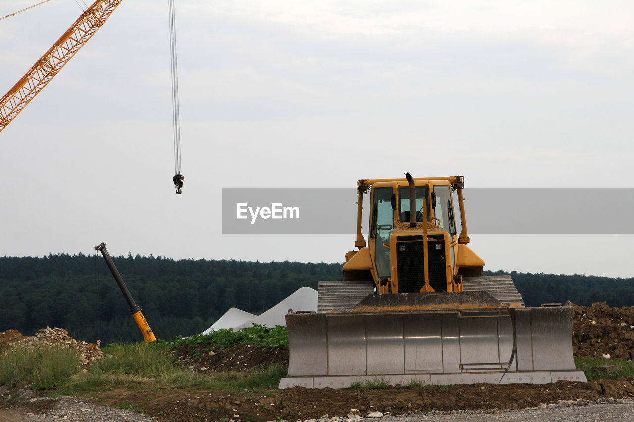 Earth mover at construction site against sky