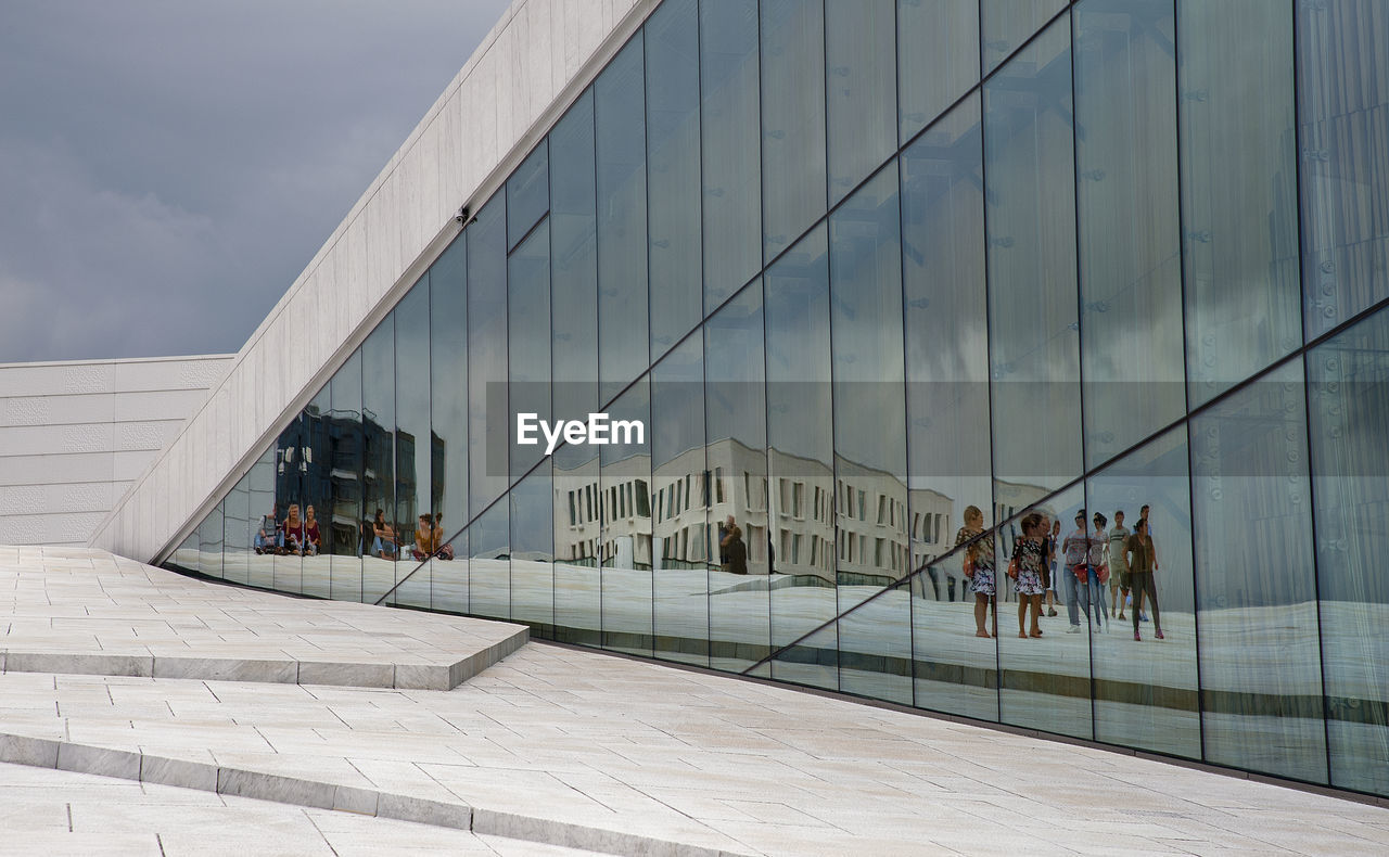 People Reflecting On Modern Building Against Sky