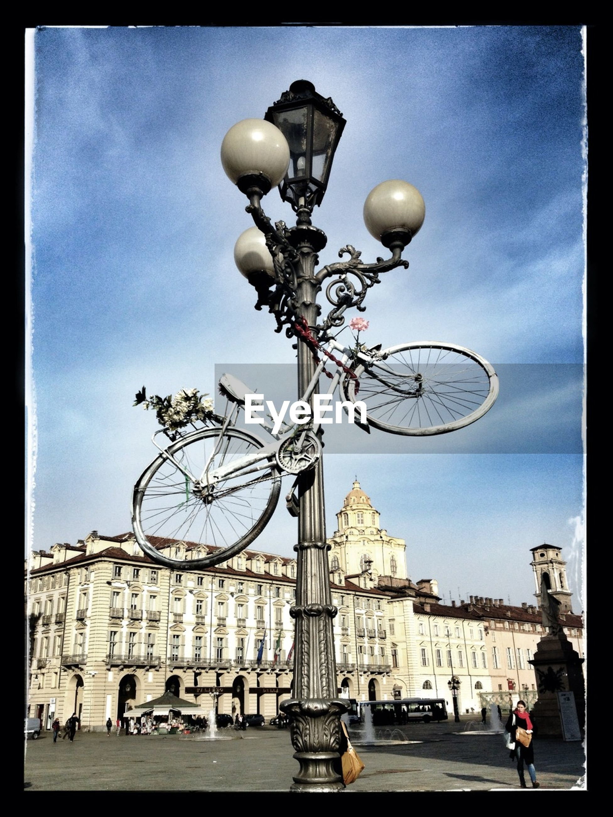 transfer print, building exterior, architecture, built structure, street light, auto post production filter, sky, street, city, transportation, lighting equipment, incidental people, low angle view, land vehicle, city life, road, car, person, bicycle, mode of transport