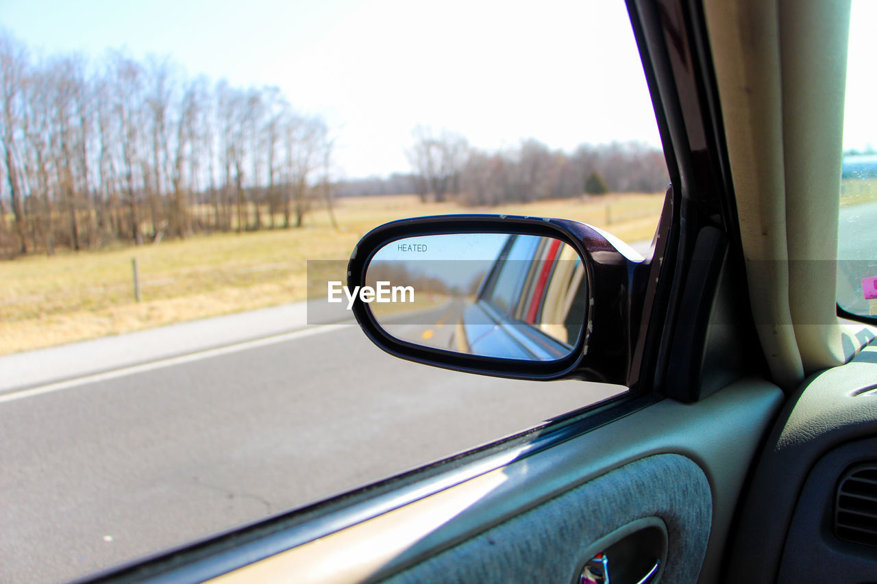 side-view mirror, transportation, car, mode of transport, land vehicle, window, day, reflection, vehicle part, no people, vehicle mirror, tree, road, road trip, nature, sky, close-up, outdoors