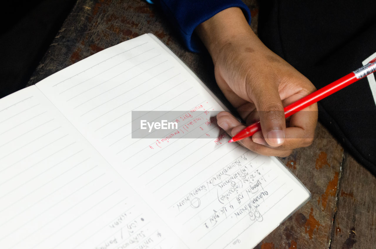 human hand, hand, real people, high angle view, human body part, holding, people, writing, indoors, table, finger, paper, human finger, pen, education, text, lifestyles, book, publication, studying