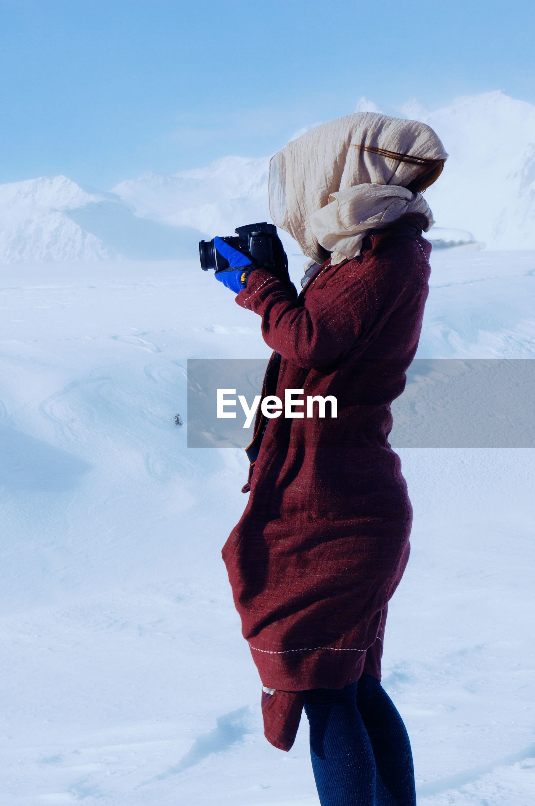 Side view of woman photographing on snowcapped mountain