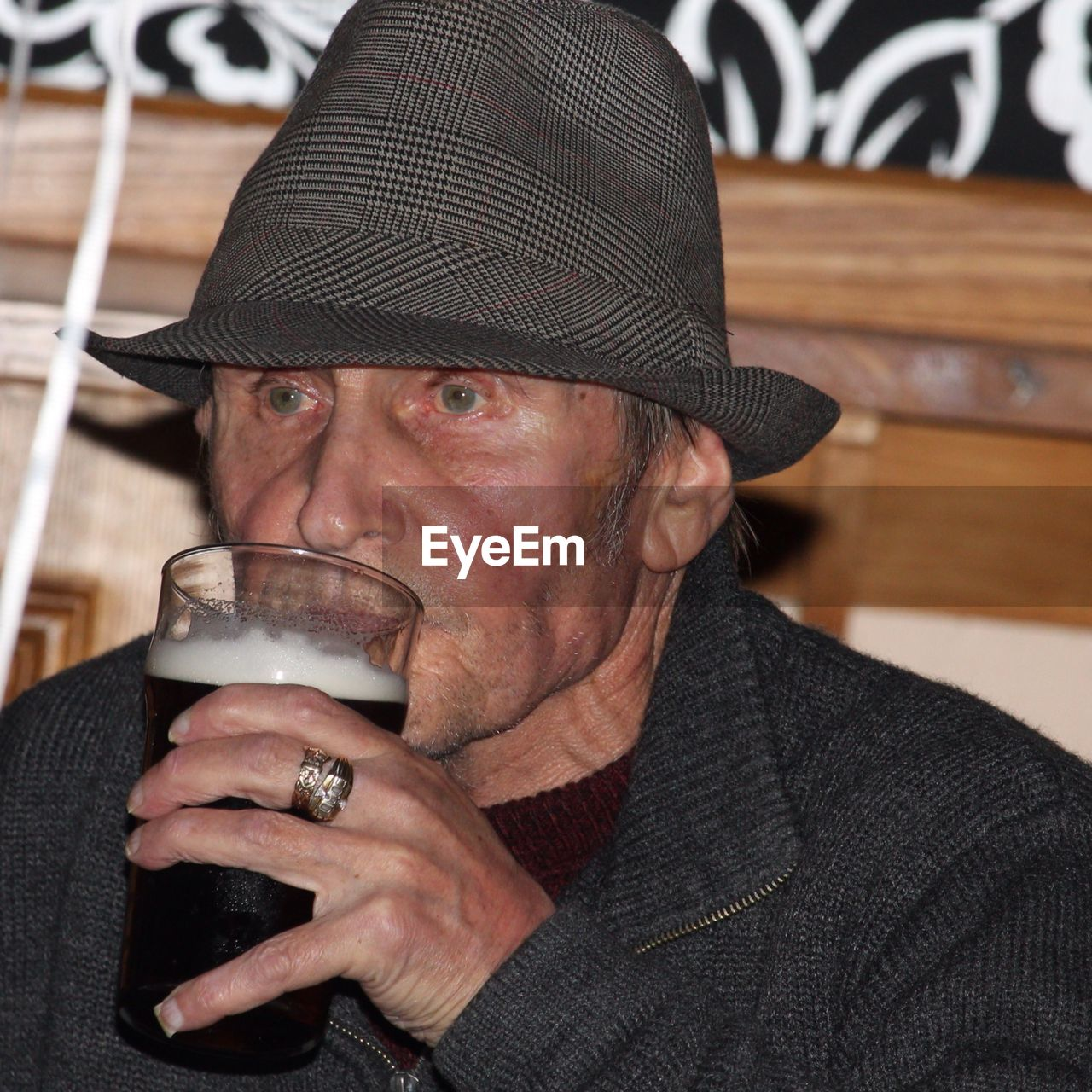 Old man wearing hat with drink