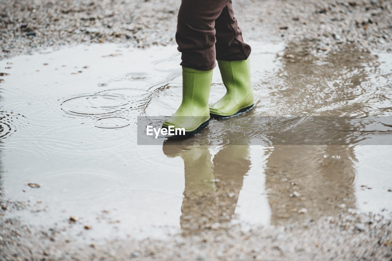 Low Section Of Person Walking On Puddle