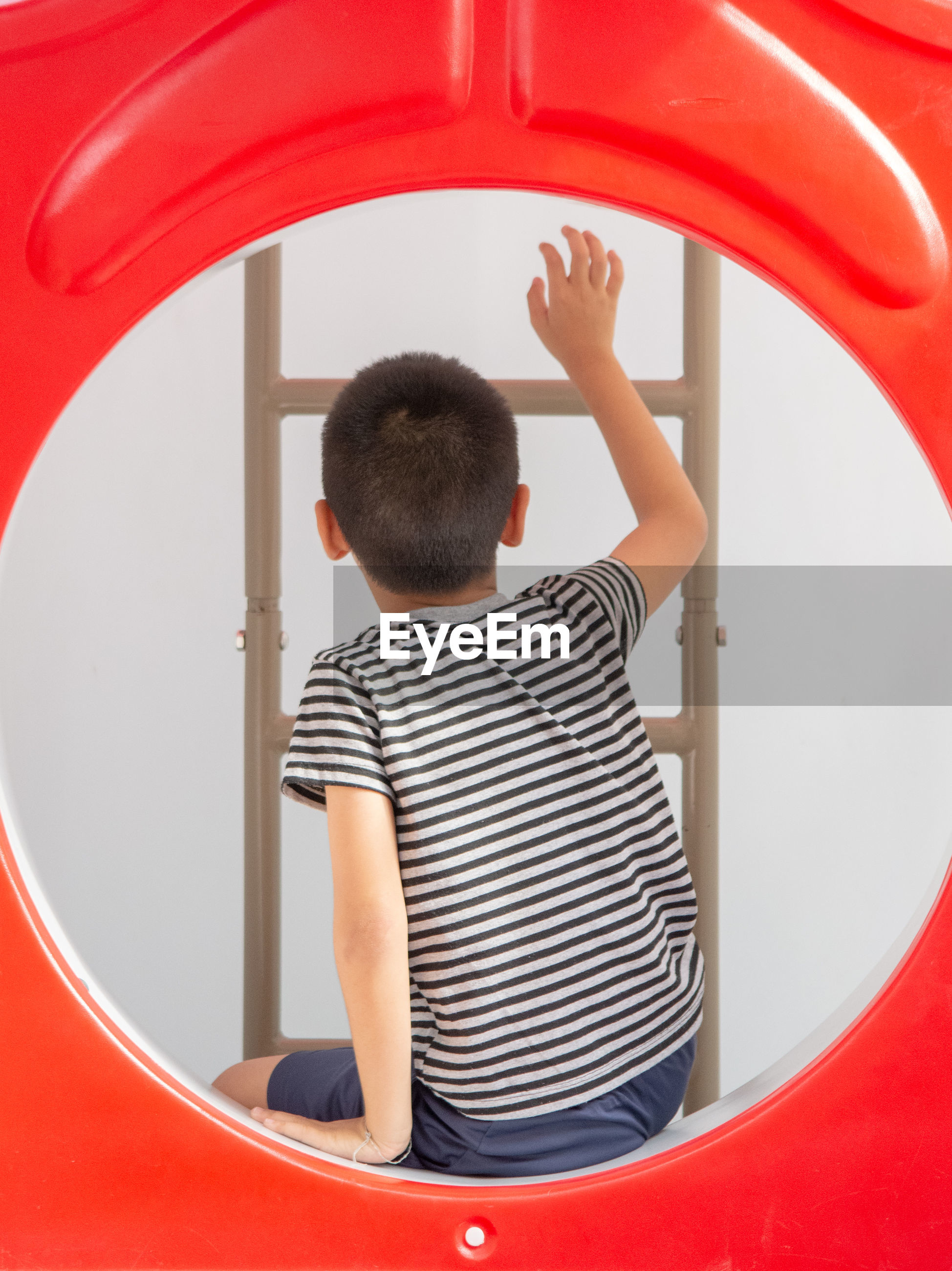 Rear view of boy climbing ladder over white background