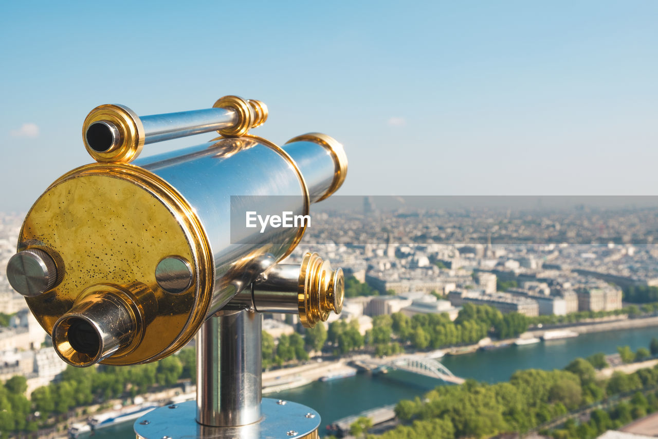 Close-up of coin-operated binoculars at eiffel tower against cityscape