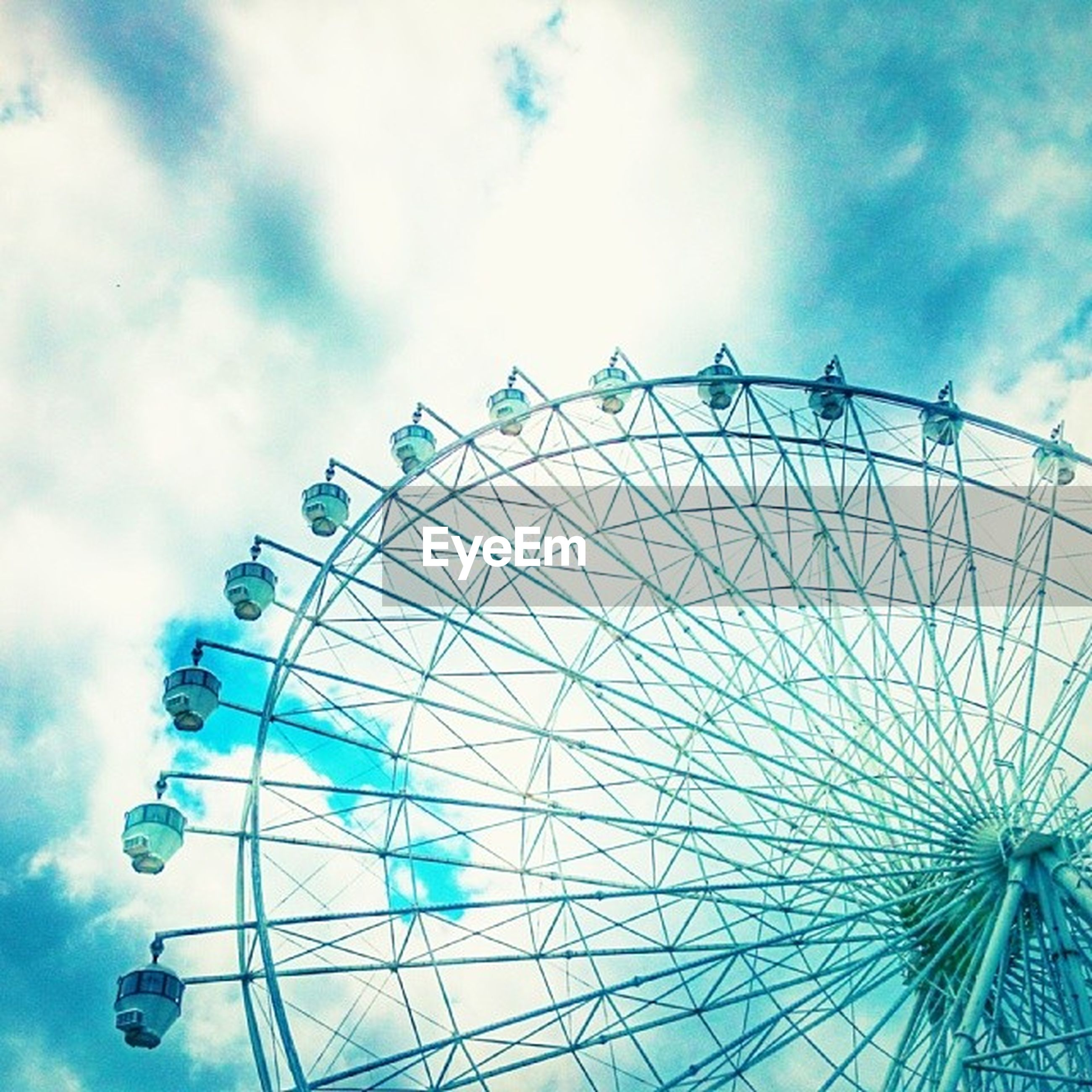 low angle view, amusement park, sky, amusement park ride, ferris wheel, arts culture and entertainment, cloud - sky, pattern, blue, cloudy, design, cloud, metal, day, built structure, fun, circle, no people, decoration, outdoors