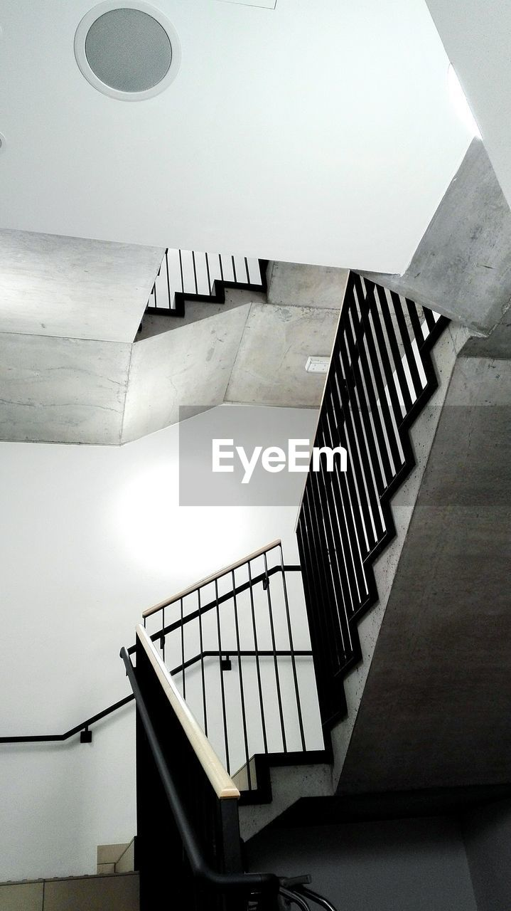 steps and staircases, staircase, architecture, railing, built structure, indoors, low angle view, no people, spiral, building, spiral staircase, day, white color, wall - building feature, absence, directly above, ceiling, pattern, directly below