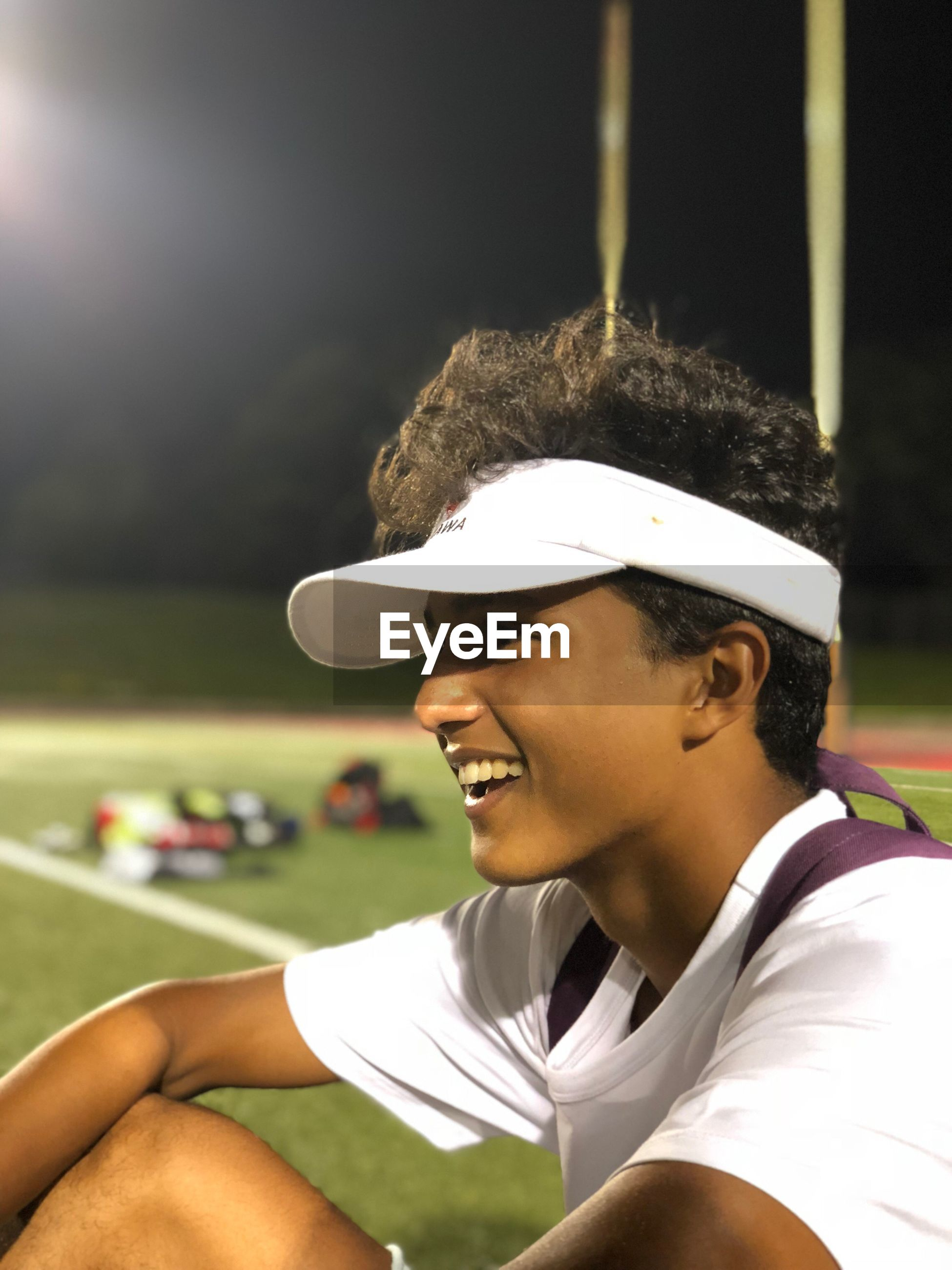 Side view of young athlete looking away at illuminated stadium